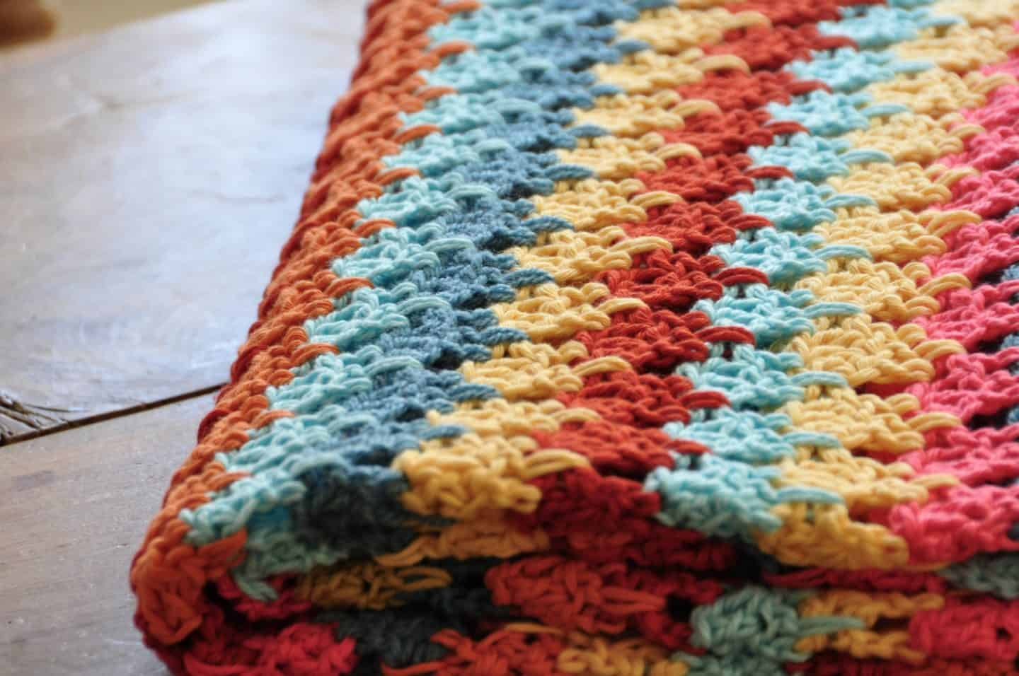 Tackle your yarn stash and learn how to crochet the larksfoot stitch with this beautiful and easy free crochet blanket pattern. With step by step photos and entire crochet pattern, the larksfoot makes the perfect baby blanket, home throw, scarf or garment that is great for a beginner.
