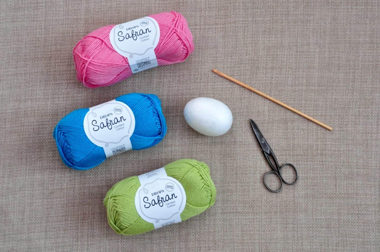 yarn, crochet hook, scissors and polystyrene egg showing how to make crochet Easter egg