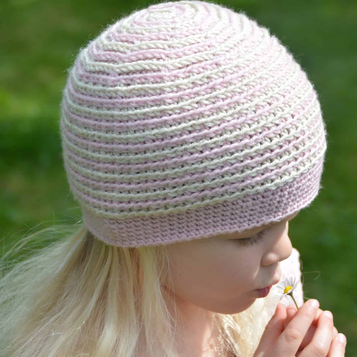 girl wearing pink and cream stripe crochet beanie hat for beginners