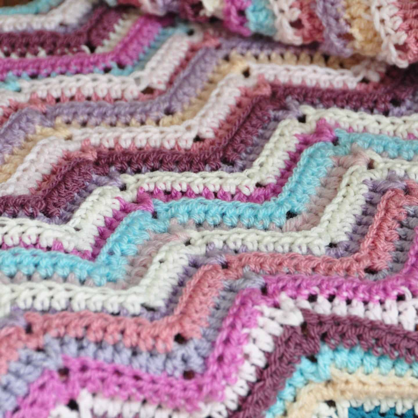 Learn to crochet the ripple stitch with this free crochet tutorial and crochet blanket pattern in both UK and US terms. Feel the retro decor vibe with bright colours or choose classic tones to make your crochet blanket perfect for you. Great for beginner crocheters.