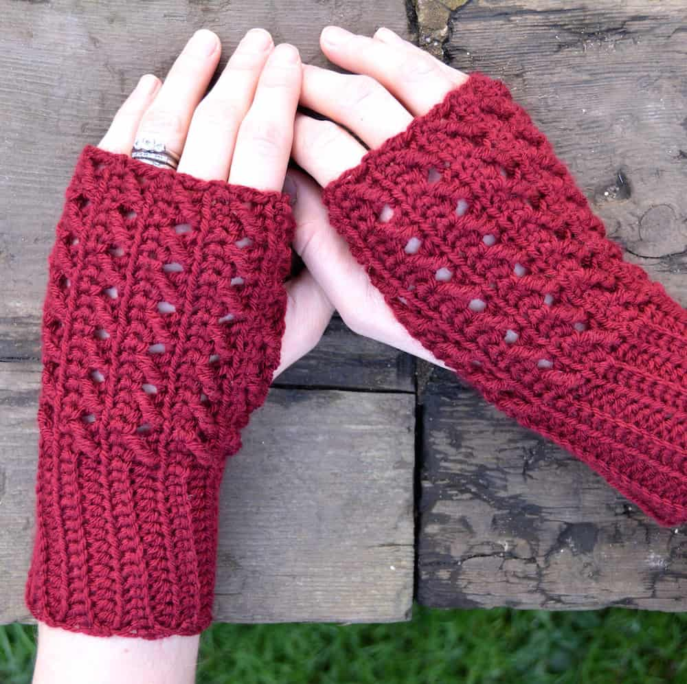 close up of female hadst wearing fingerless easy crochet mittens in red