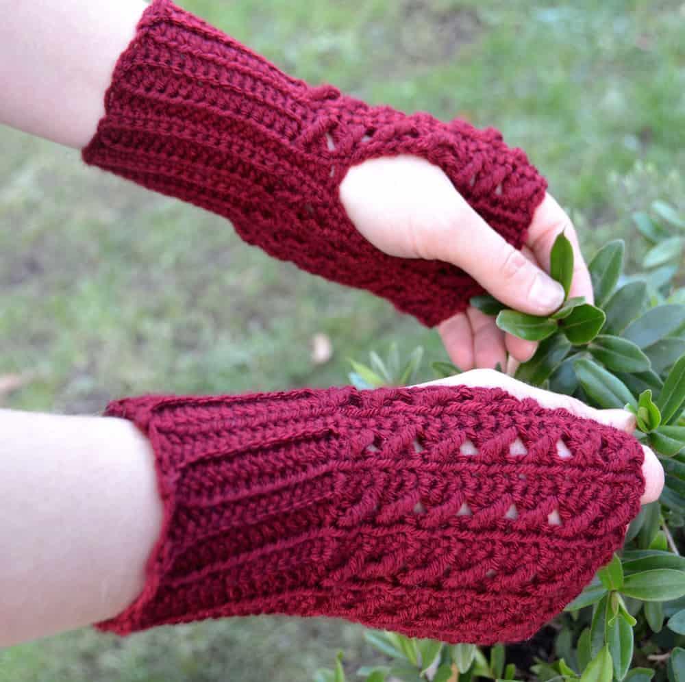 hands wearing fingerless crochet mittens holding plant leaves