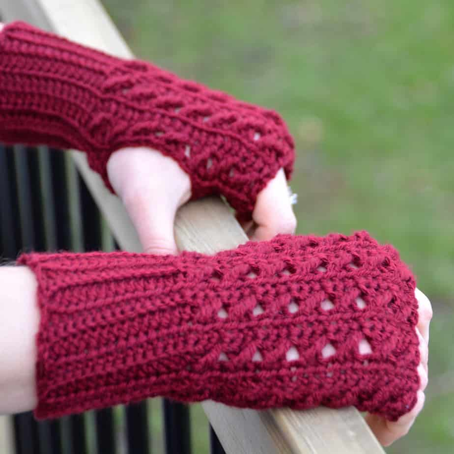 woman holding gate wearing red crochet mittens with textured design