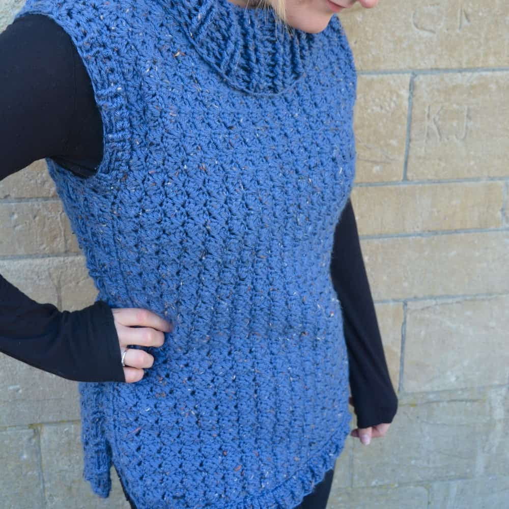 woman wearing blue tweed crochet pullover and black long sleeved top against stone wall with hand on hip