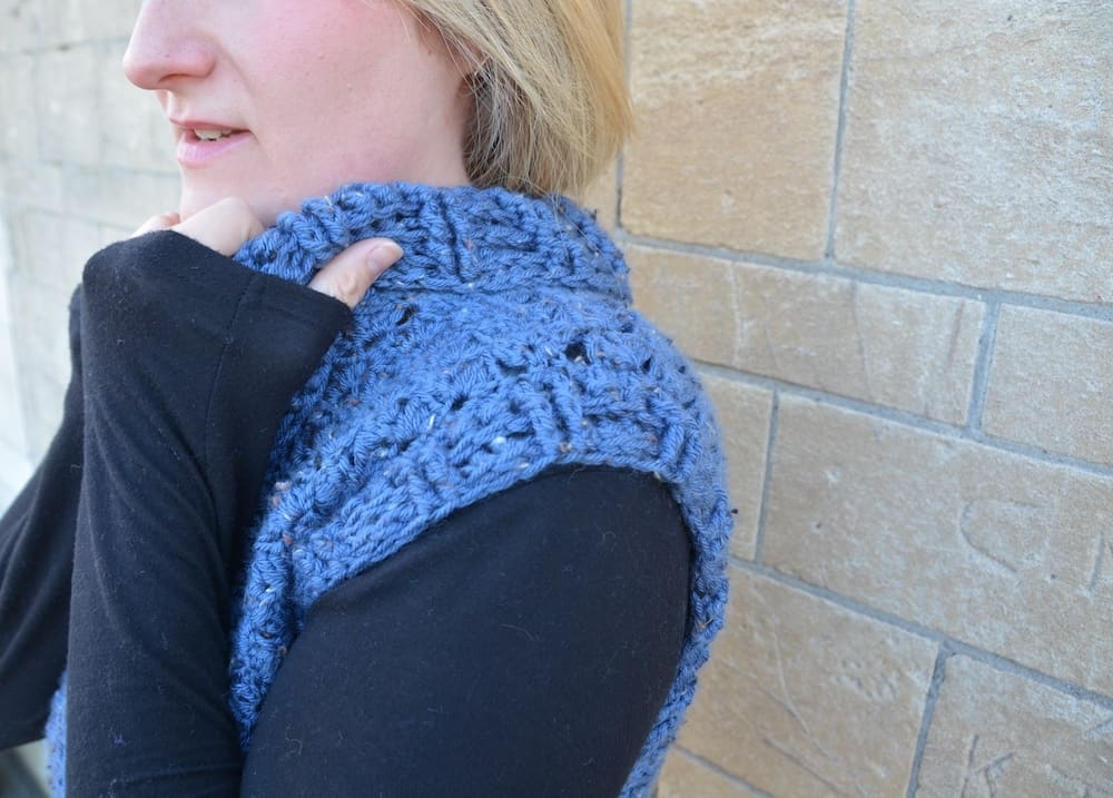 woman wearing blue tweed crochet pullover and black long sleeved top against stone wall pulling collar up