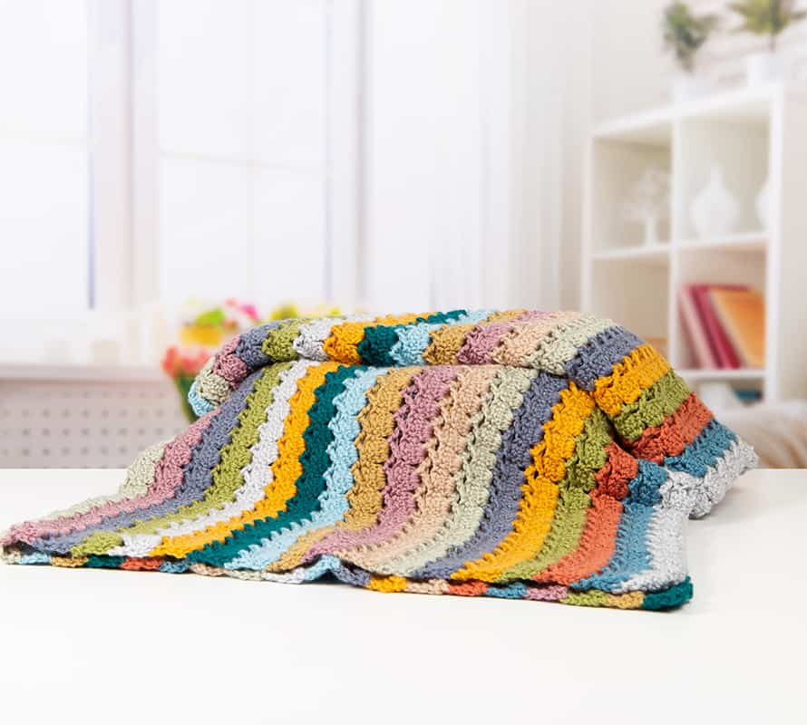 Learn to crochet the Cabbage Stitch with HanJan Crochet. A free step by step photograph tutorial to learn to crochet for beginners. The post also includes information about the free Oolong Blanket free crochet pattern by Hannah Cross.