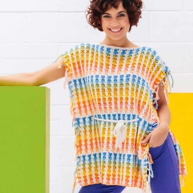 The Skittles Poncho, a bright and fun beginners crochet pattern by Hannah Cross of HanJan Crochet. A free crochet pattern to learn how to crochet in rainbow colours, a fun and easy summer make for you handmade wardrobe.