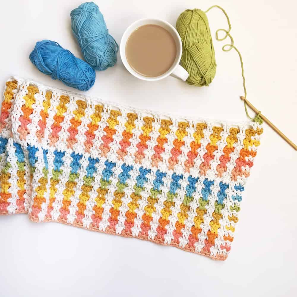 crochet poncho in progress laid out on table with crochet hook, bright yarn and a cup of tea