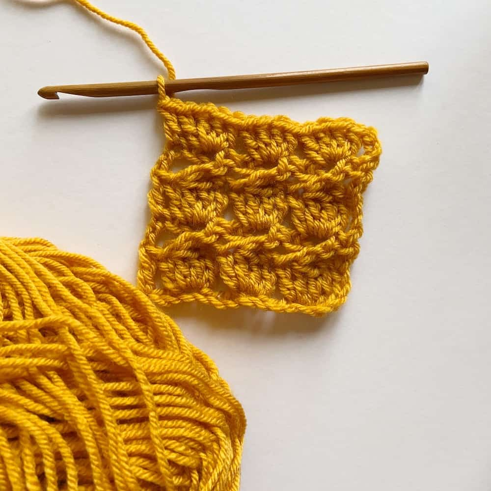The Oolong Blanket by Hannah Cross of HanJan Crochet. Learn to crochet the cabbage patch stitch with this step by step photo tutorial for the Oolong Blanket. Free PDF available from Deramores.