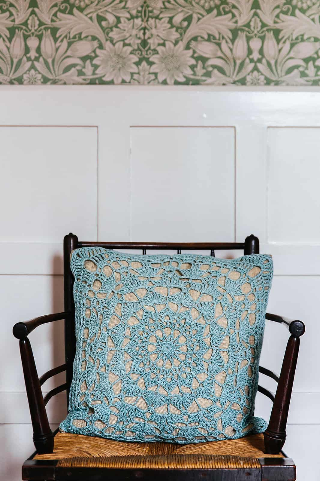 Beautiful lace crochet motif cushion on arts and crafts chair. Easy crochet home decor pattern.