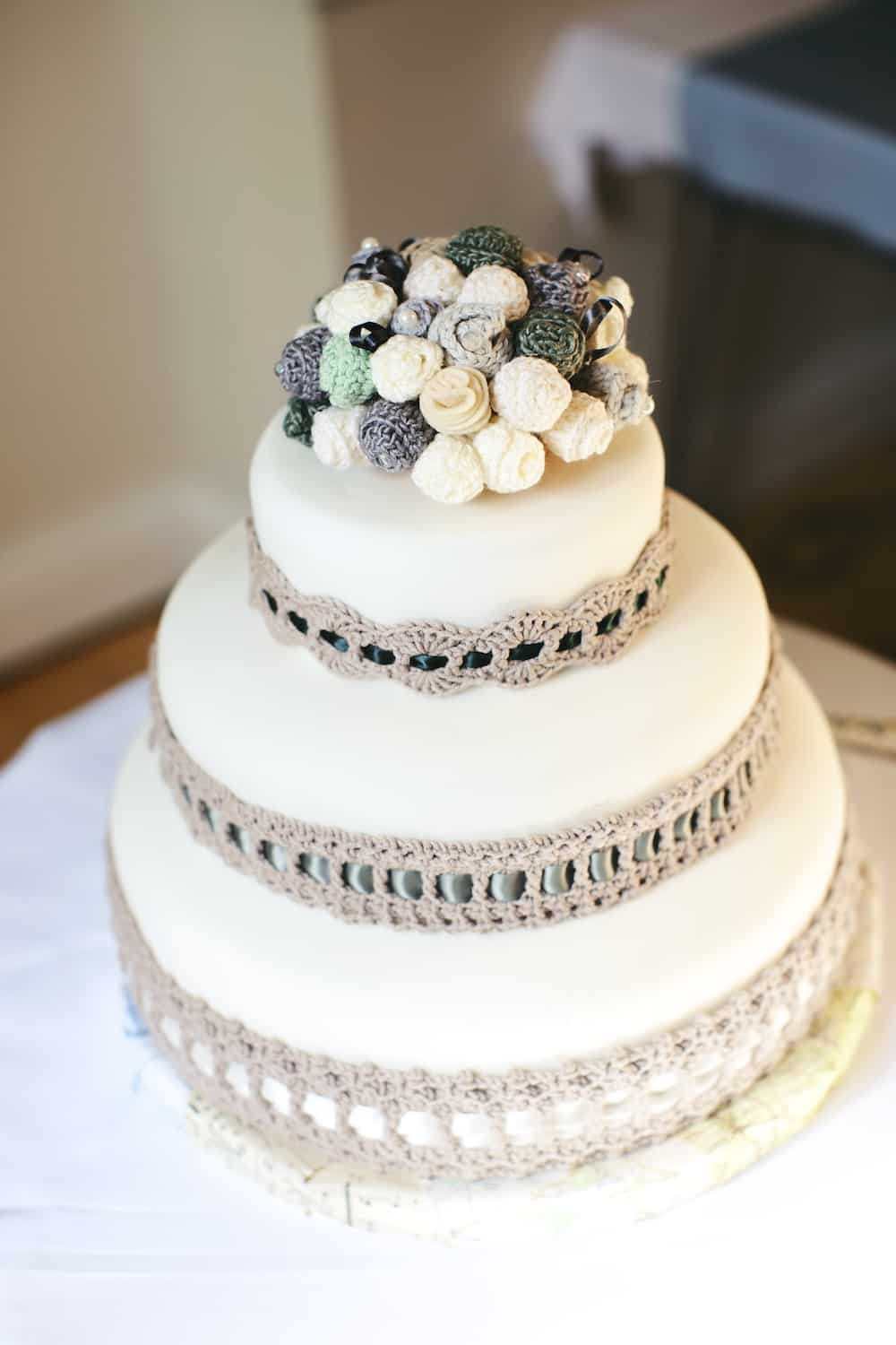 Simple and sophisticated wedding cake with crochet flower topper and crochet cake collar.