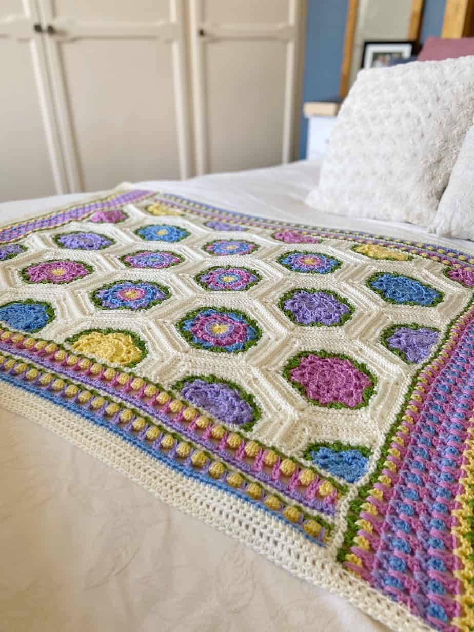 baby blooms blanket laying on bed