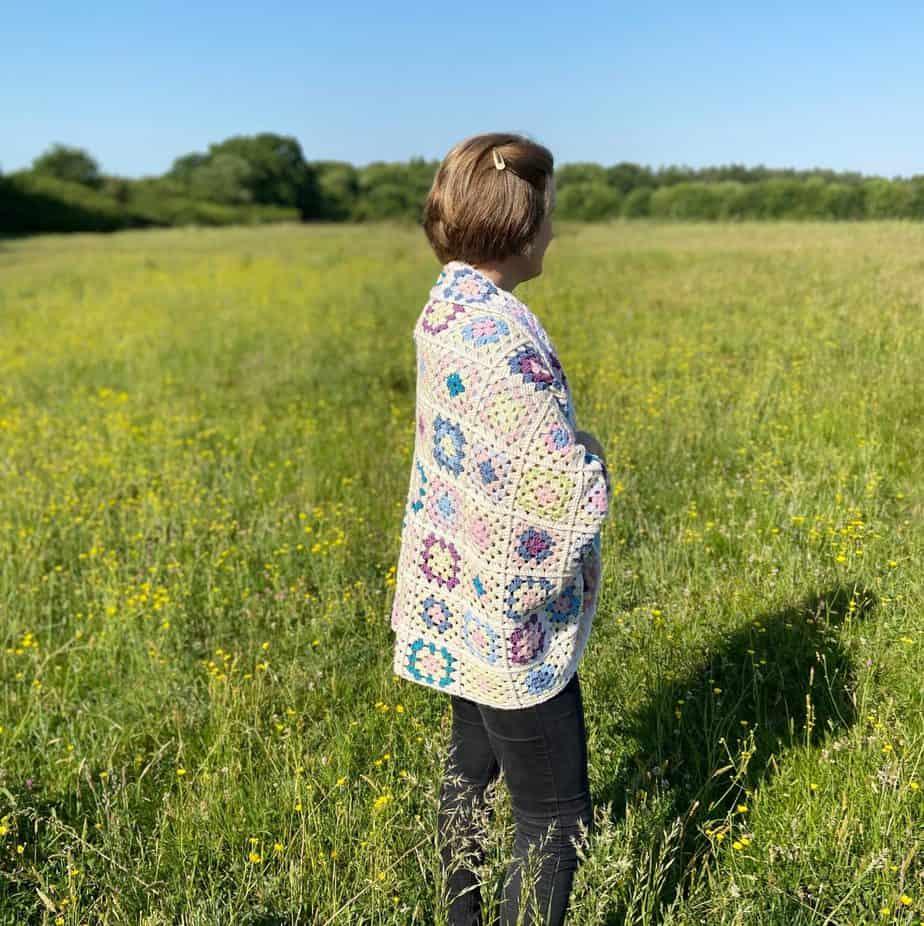 woman in field wearing granny square blanket cardigan