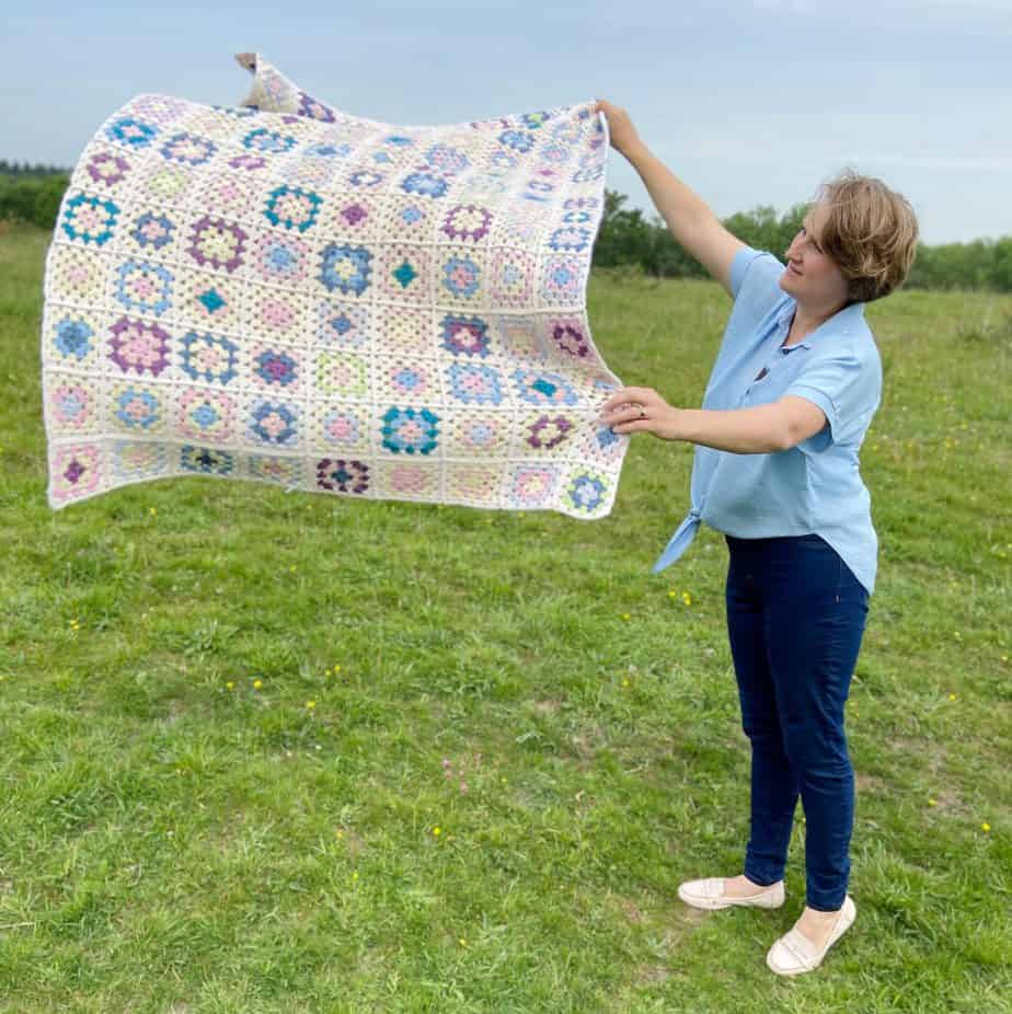 woman in field throwing a granny square crochet blanket in the air