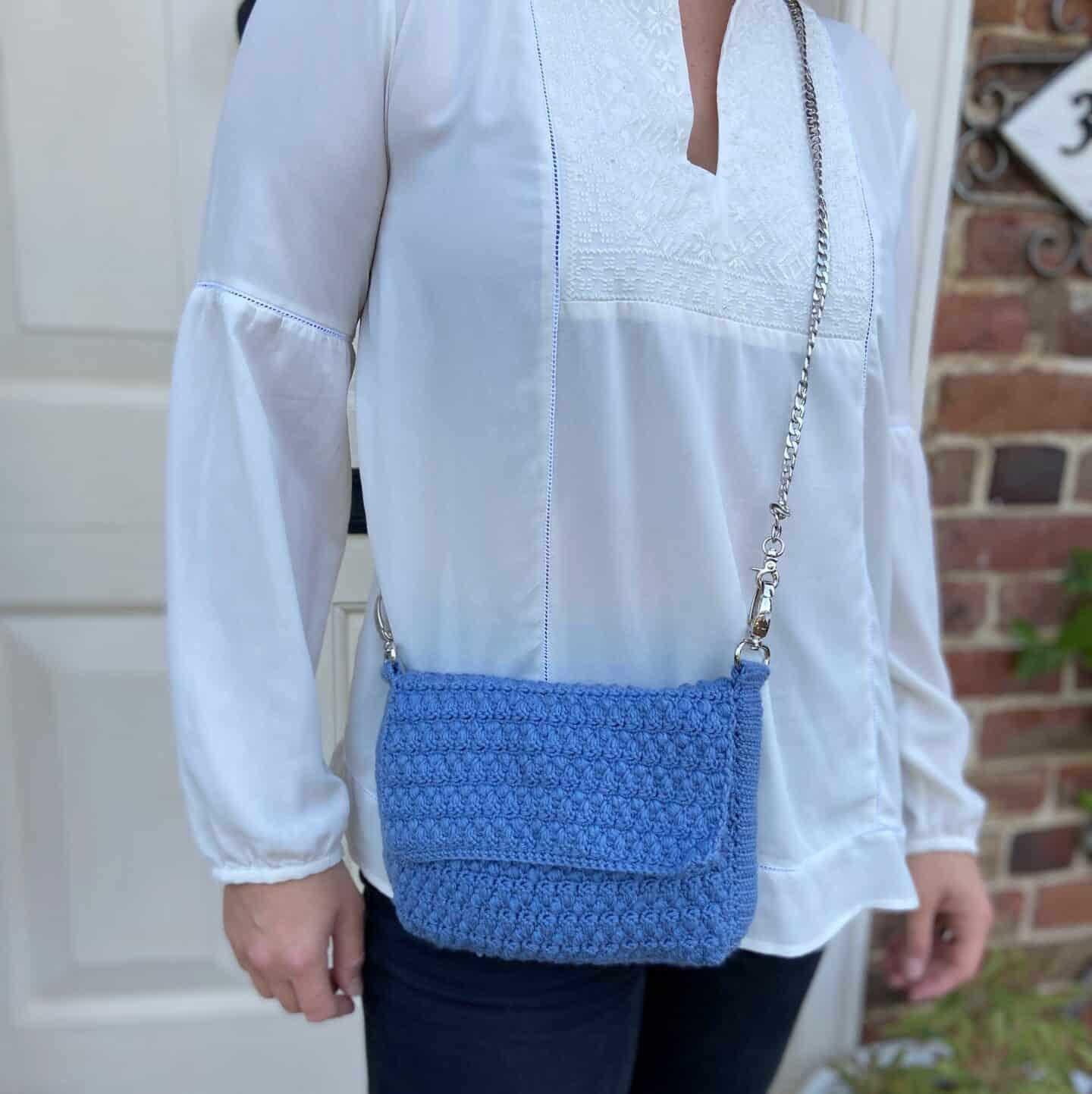 denim crochet clutch bag on woman in white shirt