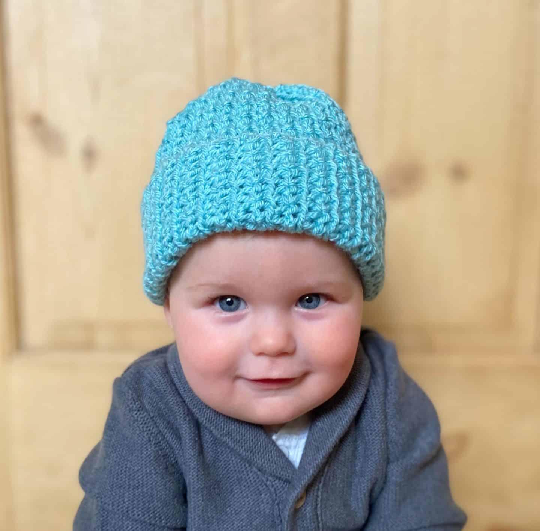 baby wearing blue crochet winter beanie hat