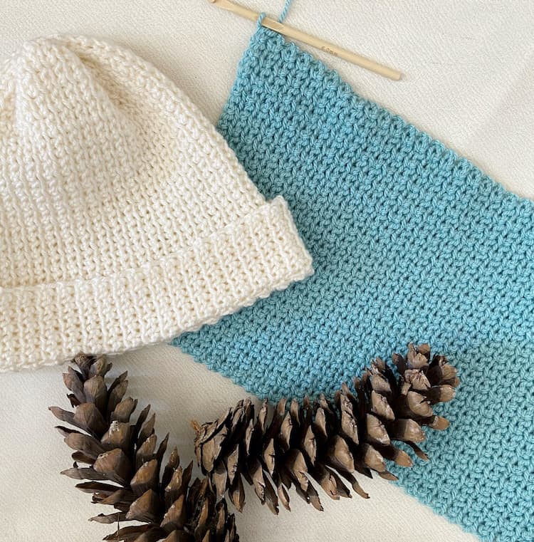 cream crochet beanie hat, crochet hook and fabric with pine cones