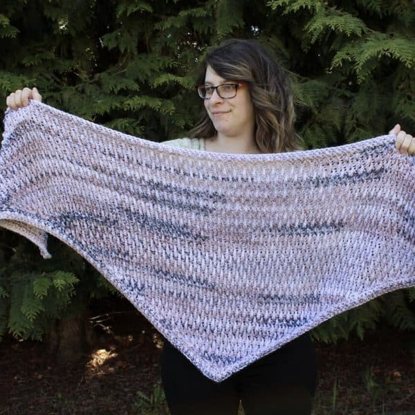 woman holding pink crochet shawl