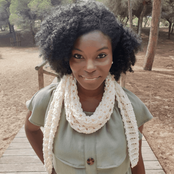 woman with afro smiling wearing cream crochet scarf
