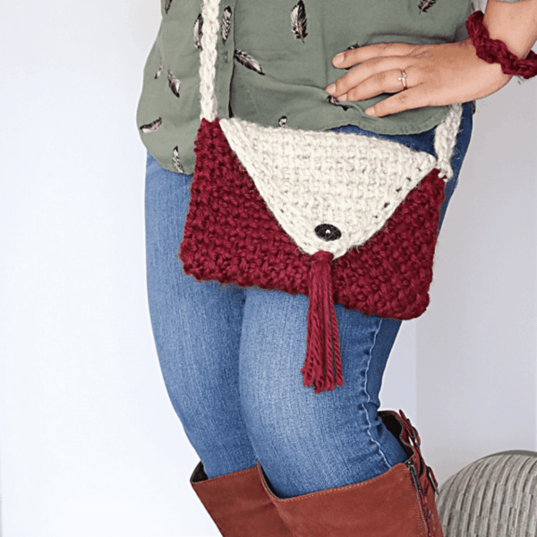 woman in boots with hands on hips wearing red and cream crochet headband with tassel