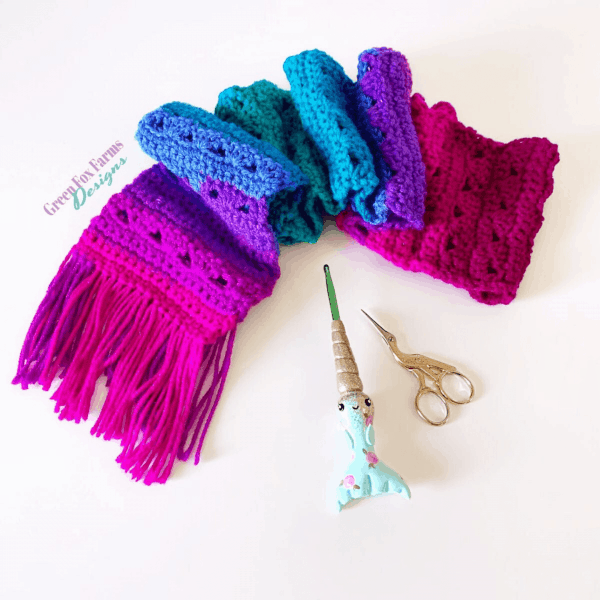 bright pink and purple scarf with crochet hook and scissors