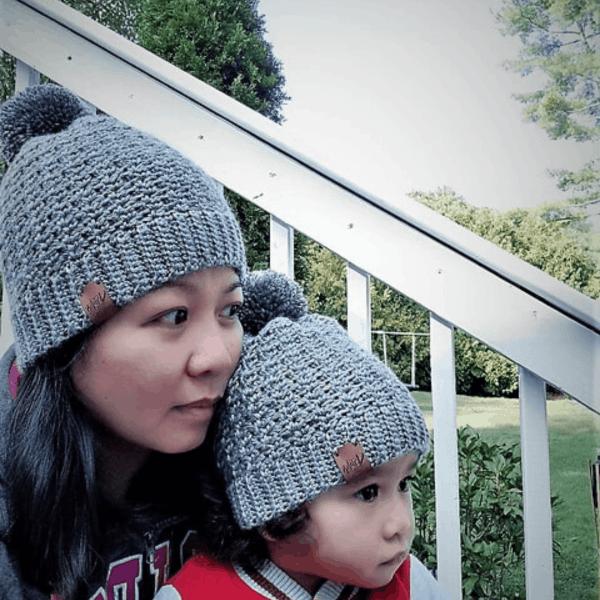 woman and child wearing matching grey crochet bobble hats