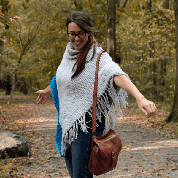 woman in woods wearing grey crochet poncho and leather handbag