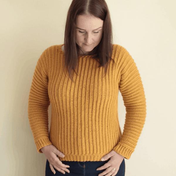 woman against white background wearing mustard yellow crochet jumper