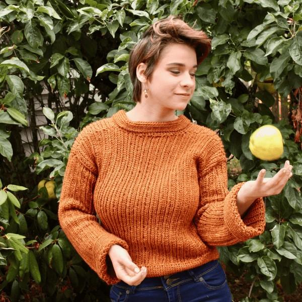 woman throwing an apple in organ crochet sweater
