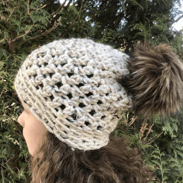 woman looking sideways wearing chunky grey crochet bobble hat