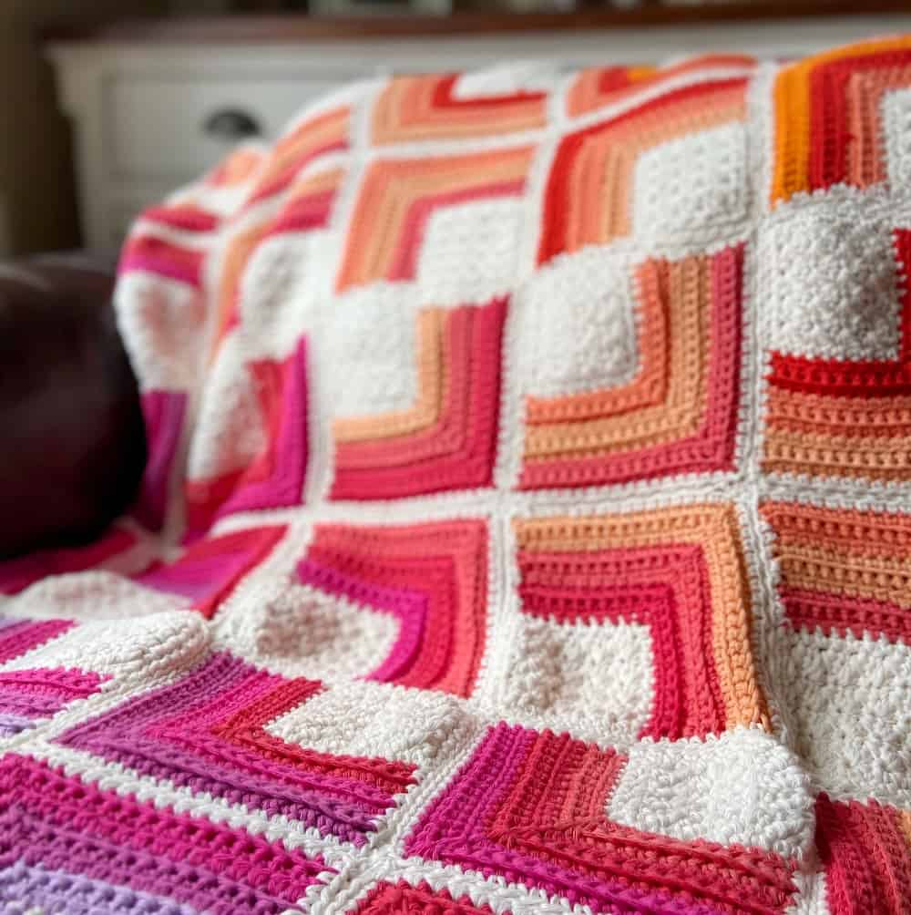 pink, purple, red, peach and white sqaure crochet blanket close up