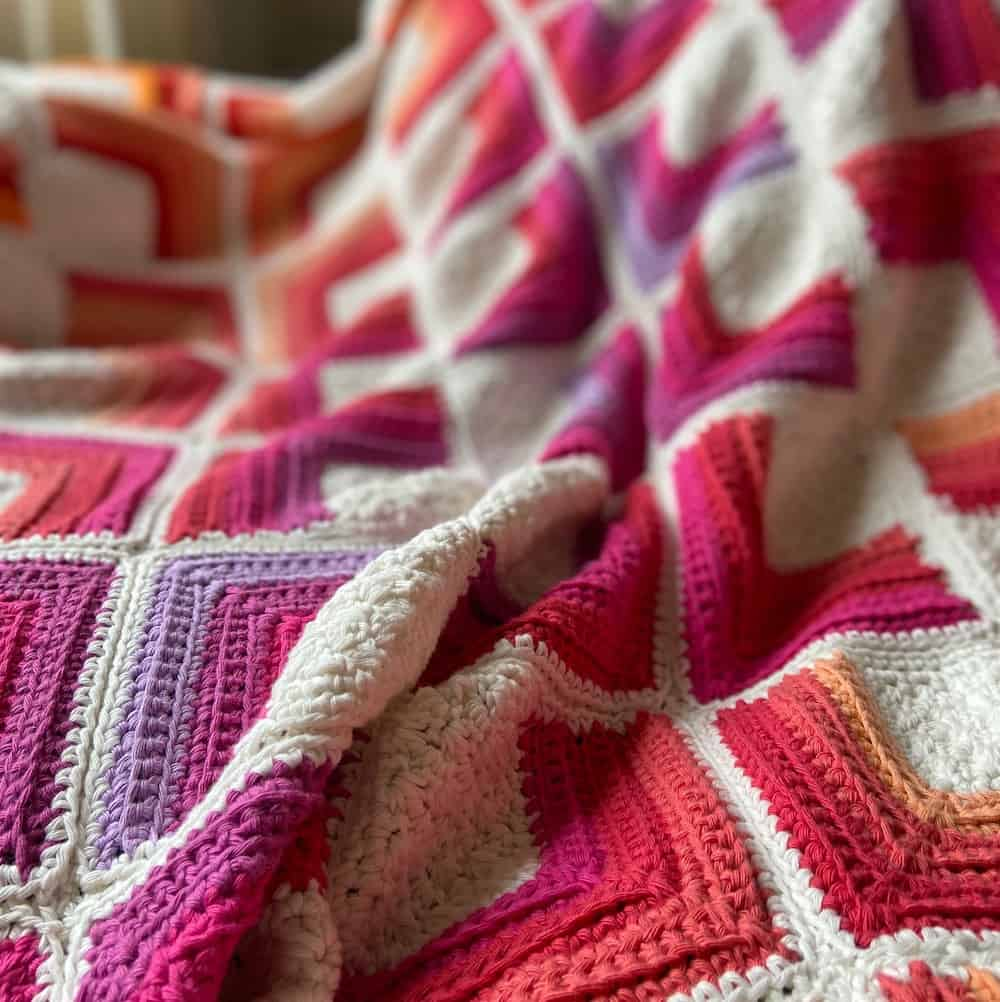 close up of square motif crochet blanket in bright and hot colours