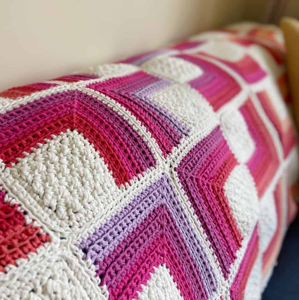lilac, purple, pink and white sqaure motif crochet blanket on back of sofa