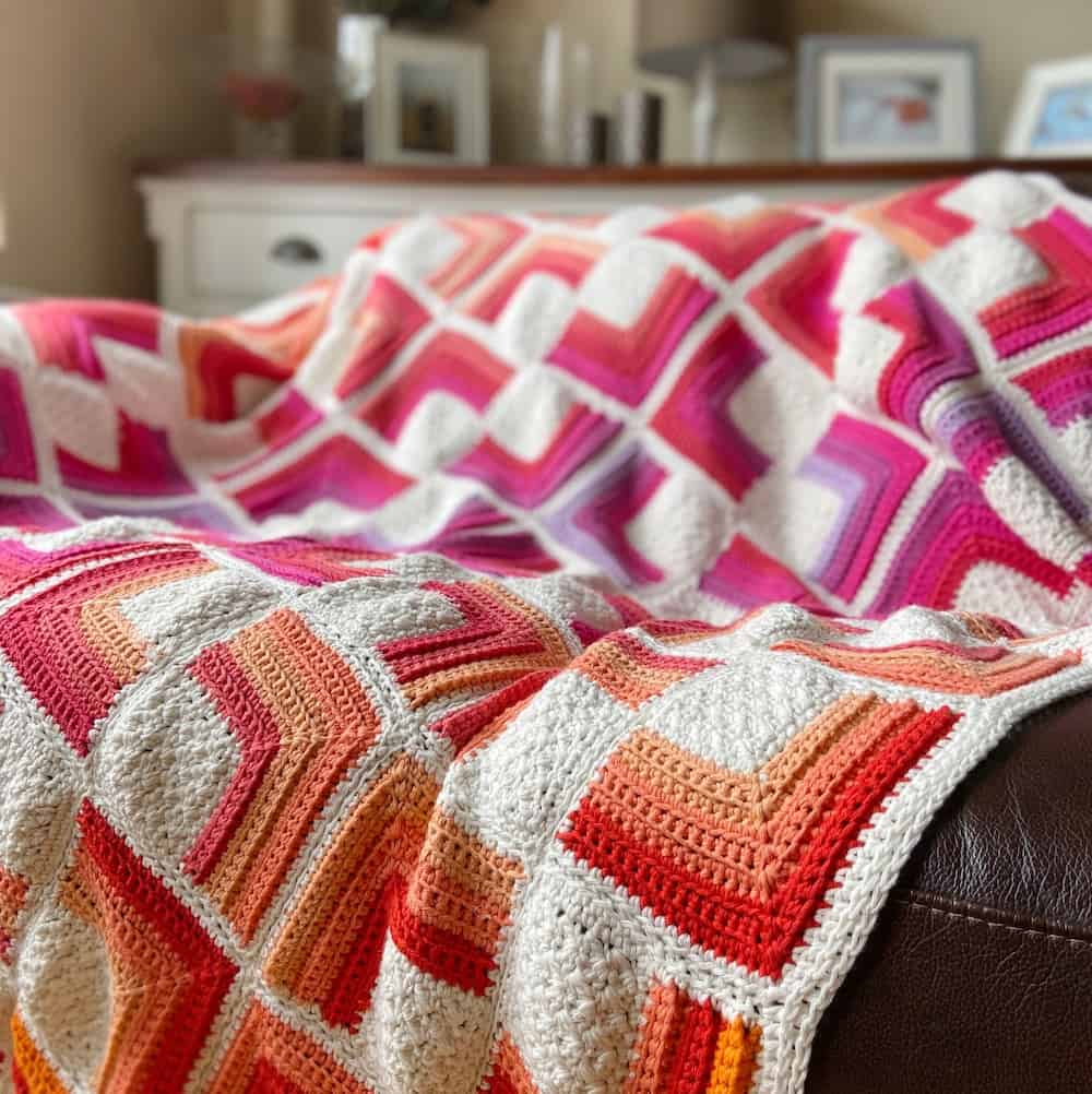 red, orange, yellow, pink and white crochet square motif blanket on brown leather sofa