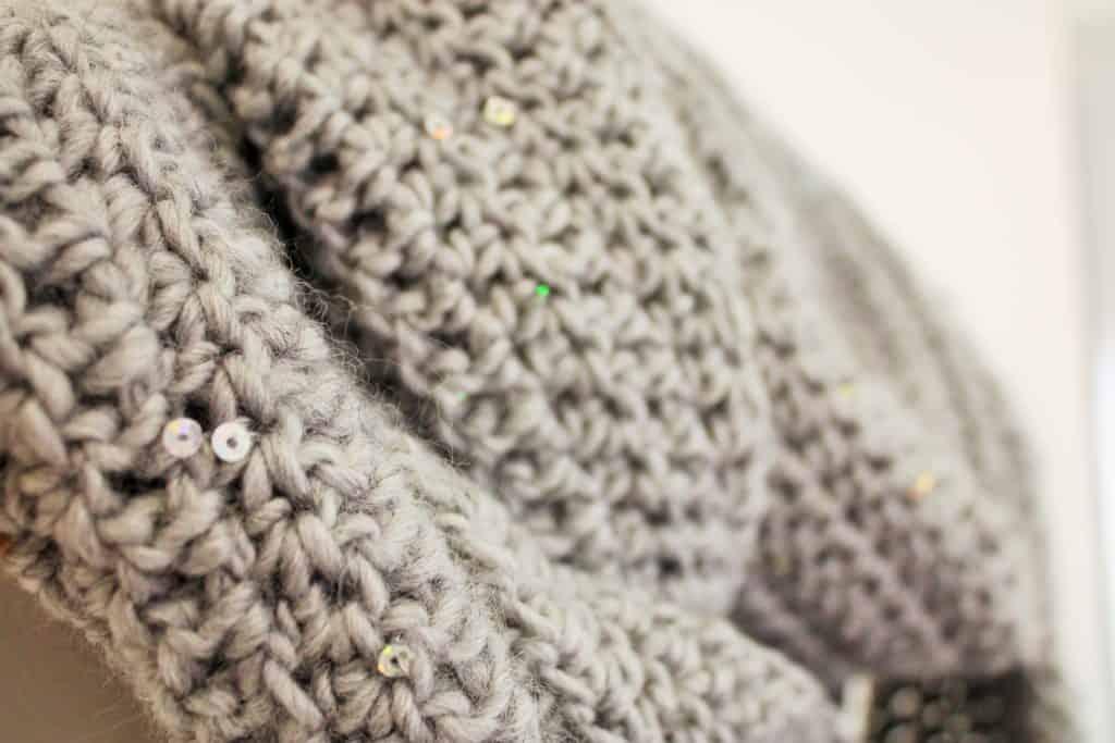 grey crochet scarf on hanger