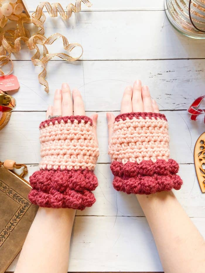 woman wearing chunky red bobble crochet fingerless mitts laid on table with gold Christmas trimmings