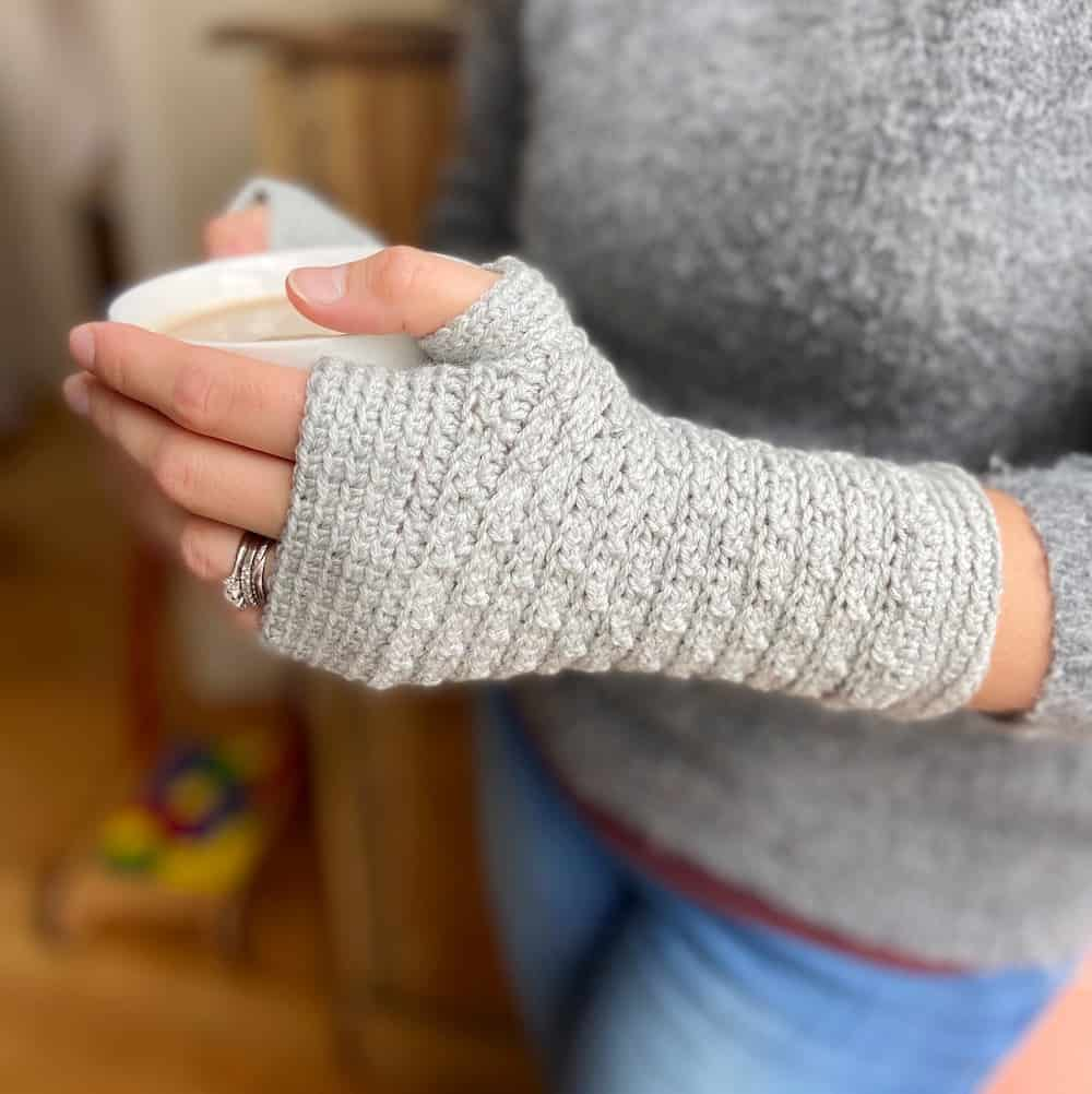 woman holding cup of coffee wearing grey fingerless crochet mittens