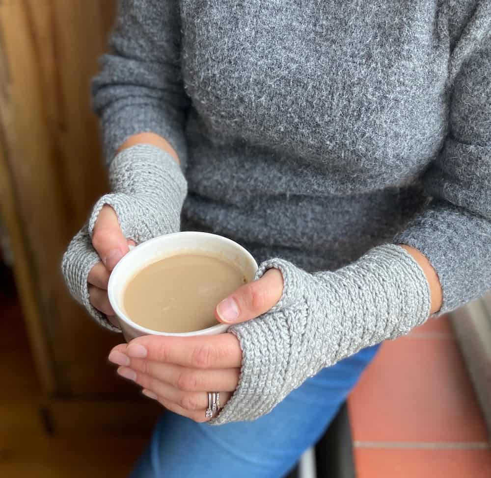 image of woman's hands holding coffee cup wearing modern grey crochet gloves