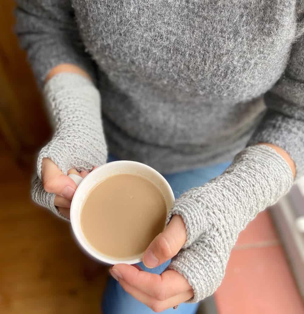 overhead photo of woman holding coffee cup wearing easy crochet gloves