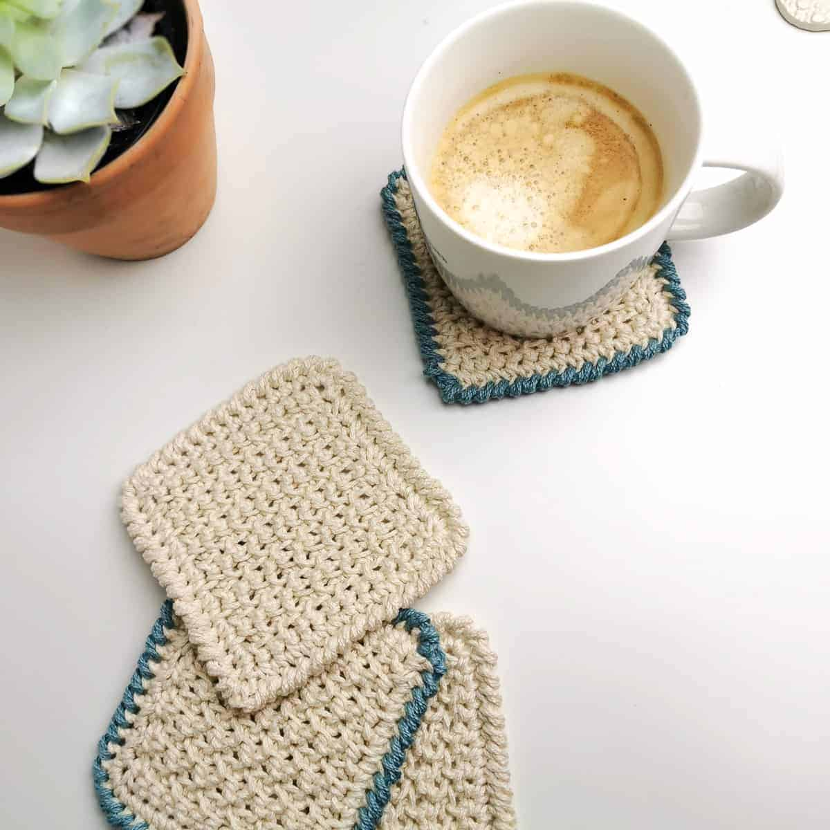 easy crochet coaster in cream and blue with a milky cup of coffee and house plant