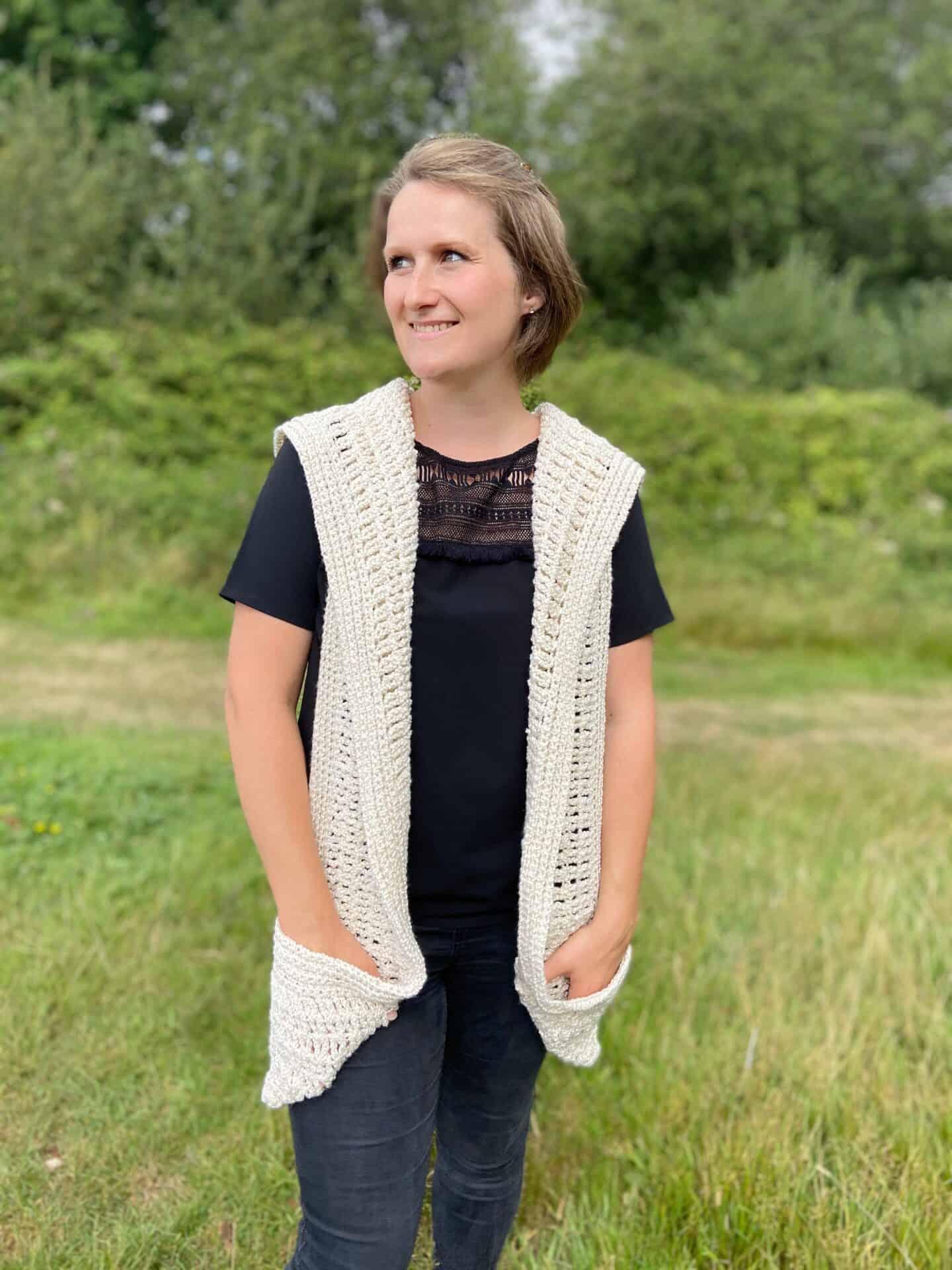 woman in field wearing hooded cream crochet pocket shawl