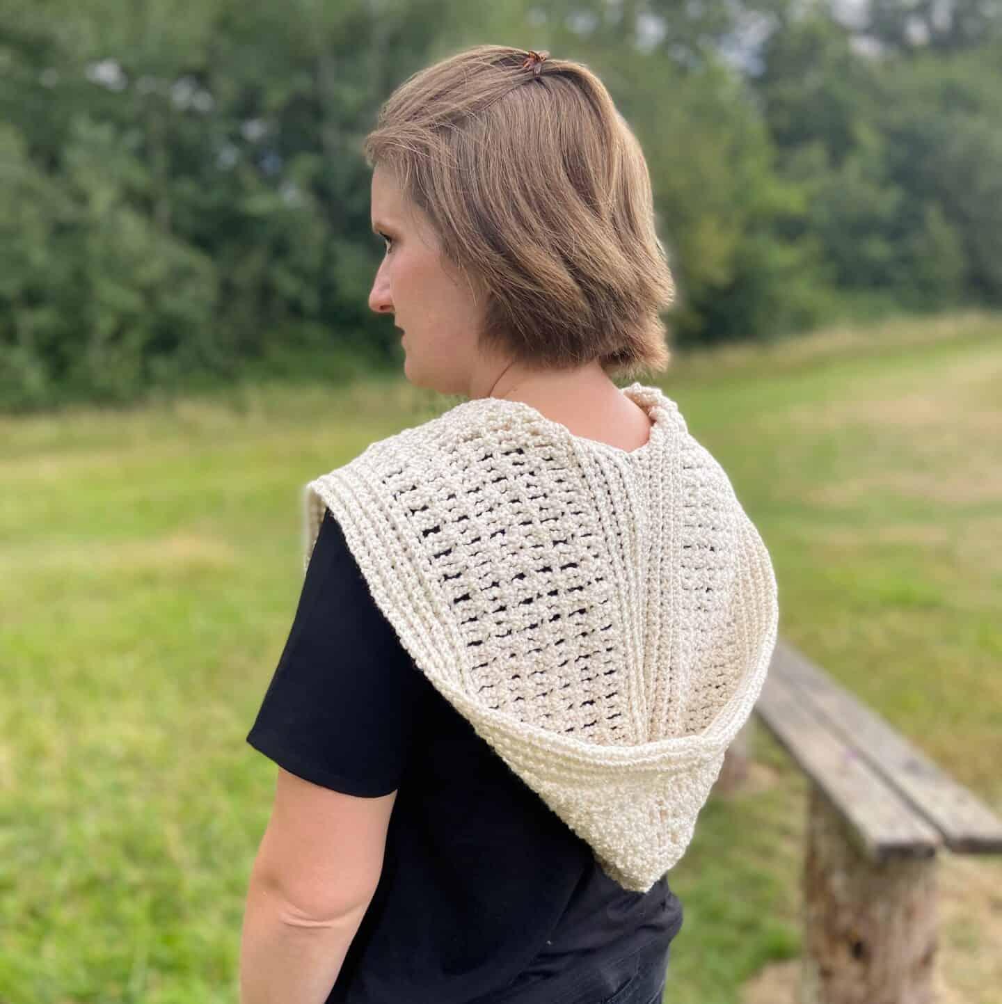 woman in field wearing hooded crochet scarf