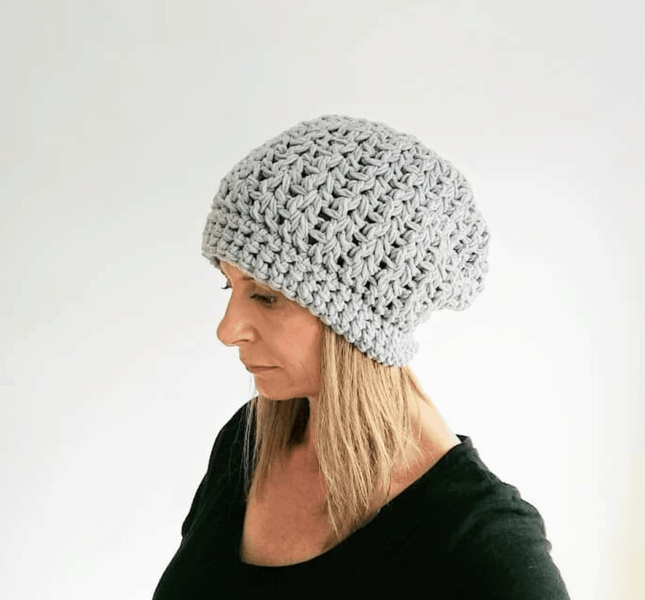 woman wearing black top and slouchy grey modern crochet beanie hat