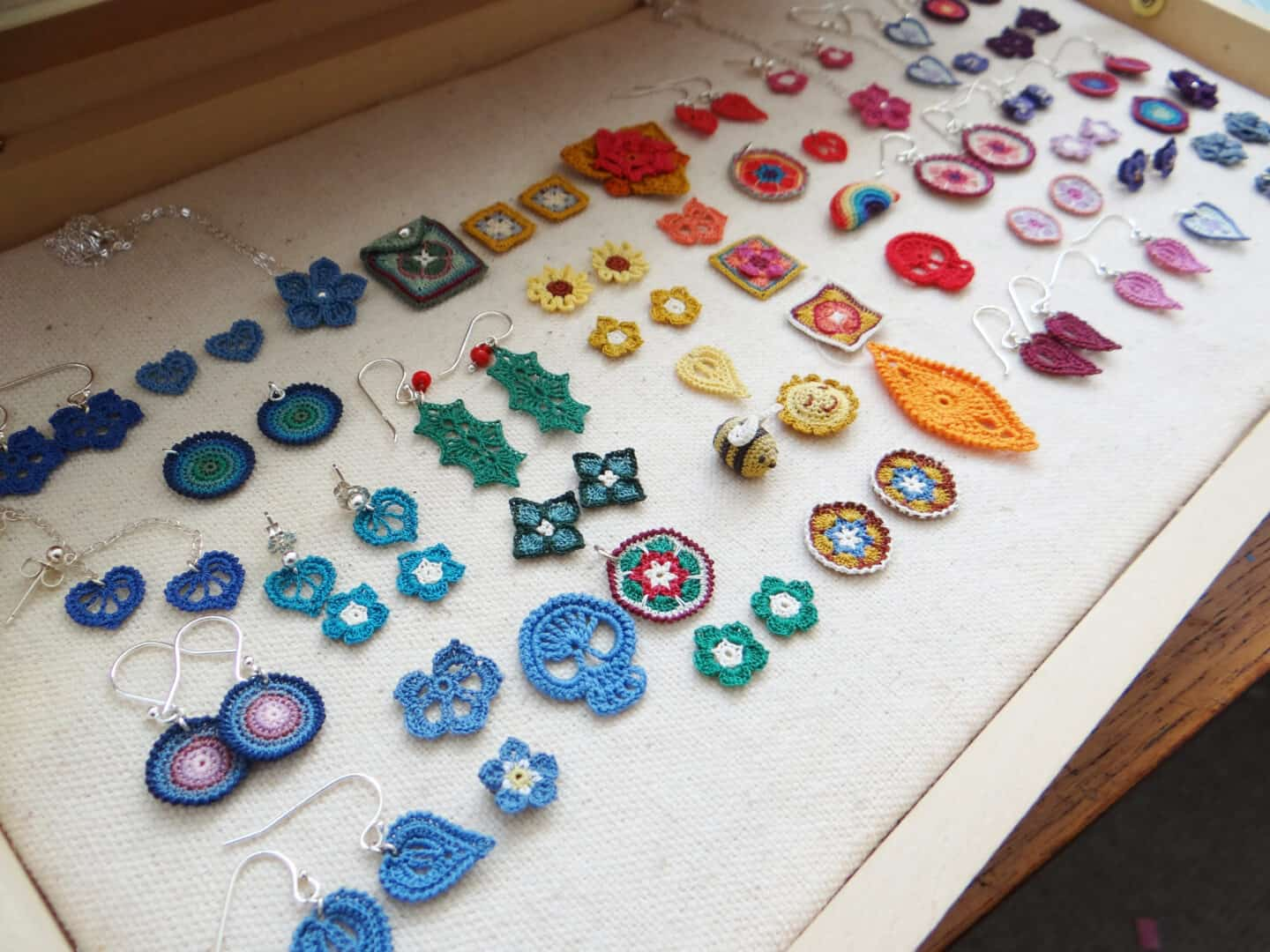 micro crochet earrings and motifs laid out in wooden presentation box, including holly leaves, granny squares, tiny flowers, skulls, bumble bees and more