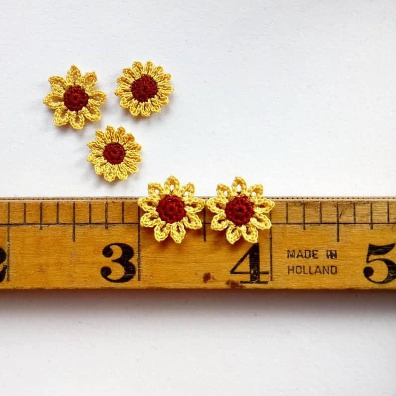5 tiny micro crochet sunflowers on a vintage ruler