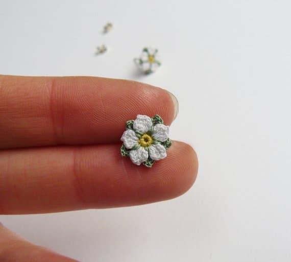 tiny micro crochet white rose flower held on two fingers