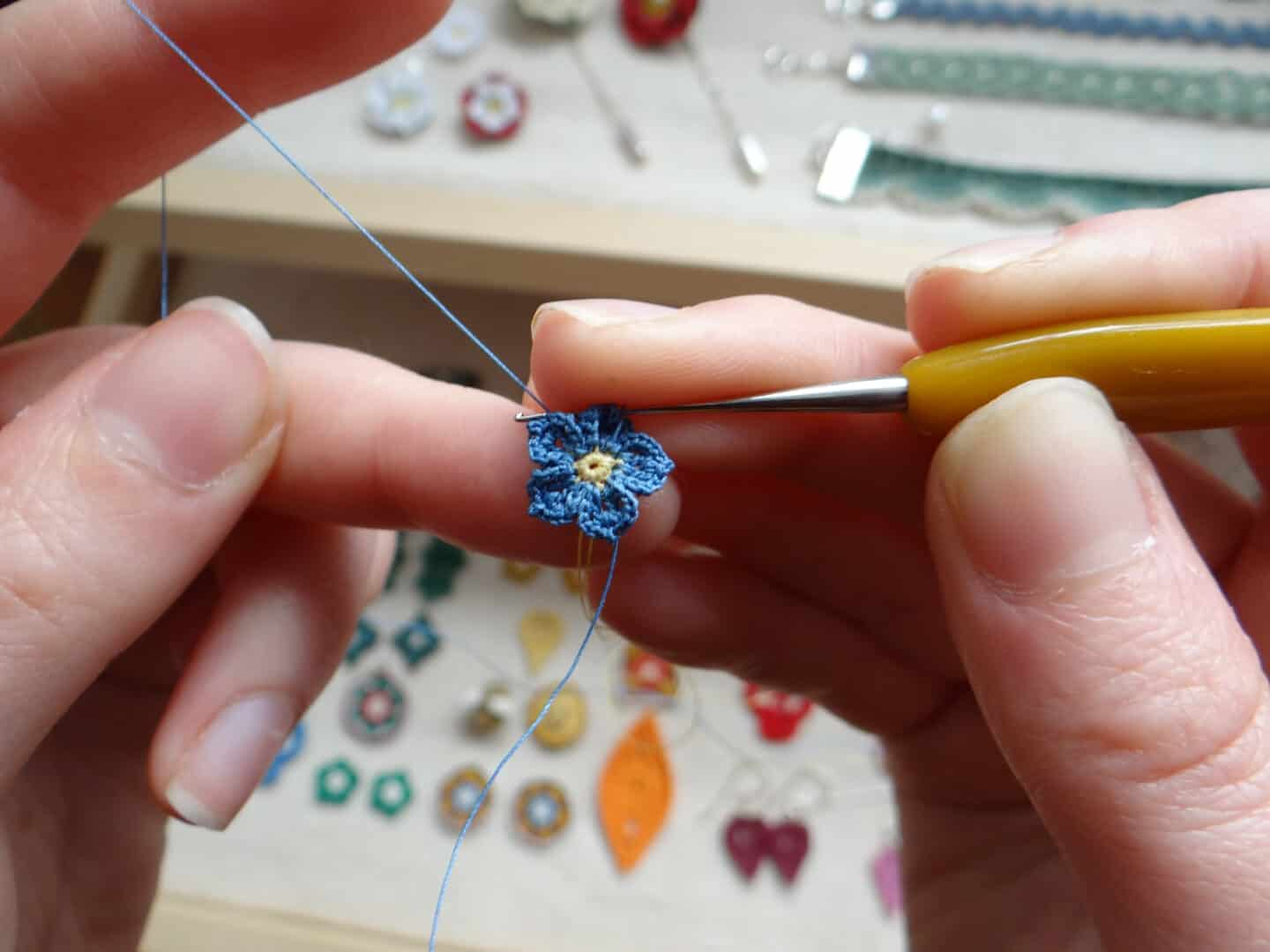 tiny micro crochet forget me not flower being crocheted with hook in hands