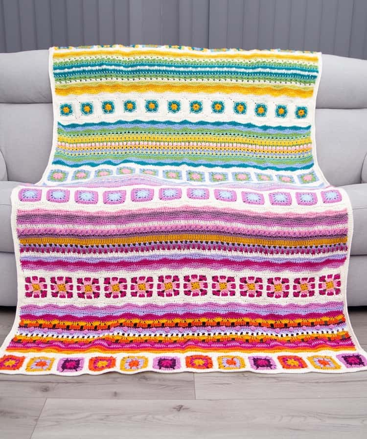 mindfulness crochet blanket with granny squares and stripes in bright colours on grey sofa