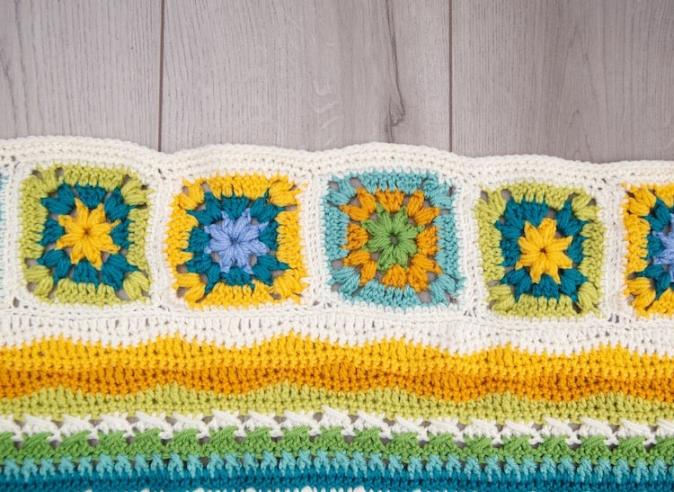 crochet blanket granny squares in bright yellow, blues and greens with white border