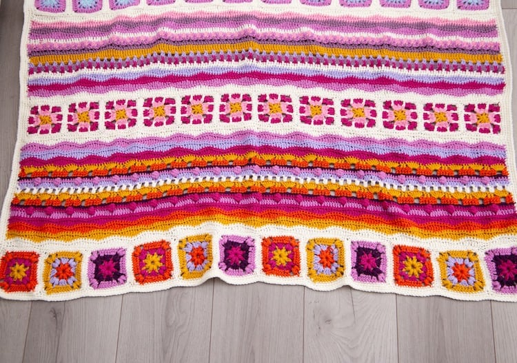 bottom of mindfulness crochet blanket in bright and uplifting colours laid on floor